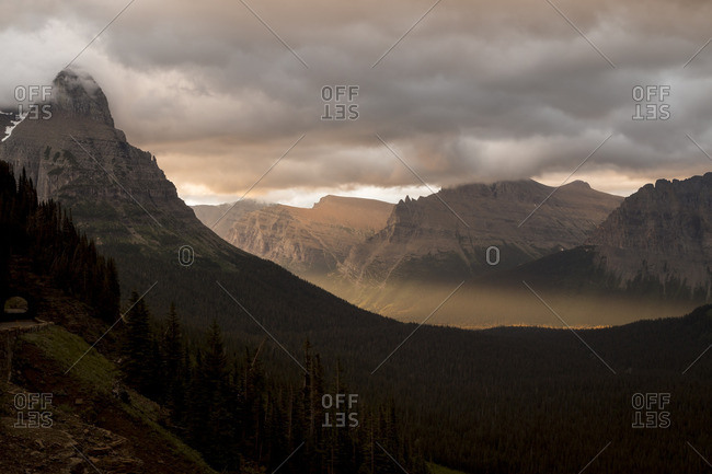 Sunlight bursts into a mountain valley as is squeezes between clouds and cliffs to provide a beam of golden light onto the valley floor
