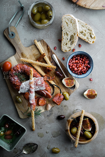 Cured meats and fruits appetizer on a cutting board