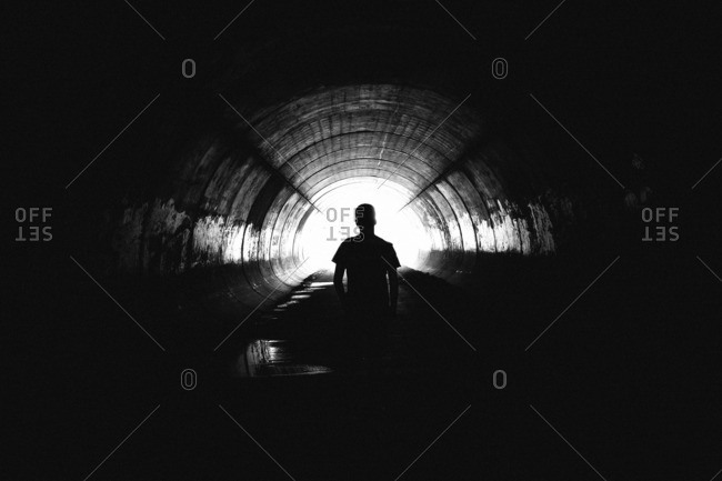 Silhouette of a person standing deep in a tunnel
