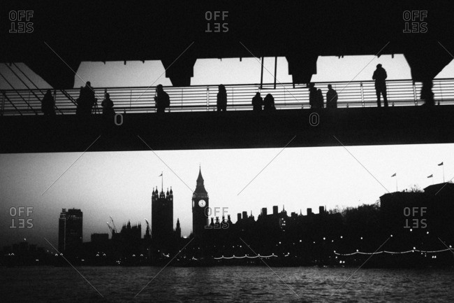 Pedestrians on a bridge looking at the London skyline