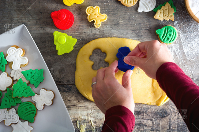 Woman cutting Christmas shapes from cookie dough
