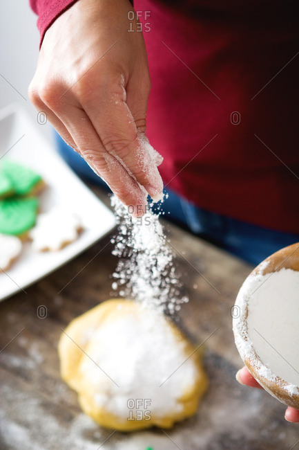 Hand of a woman sprinkling flour on cookie dough