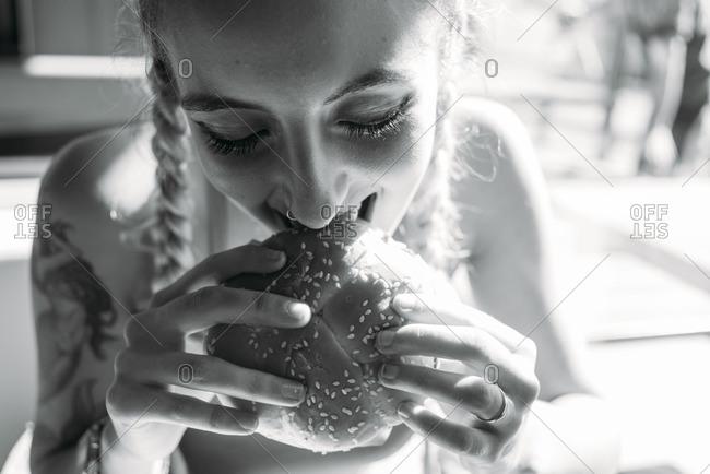 Young woman biting a large burger