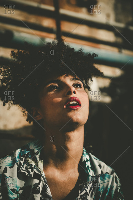 Stylish young woman gazing into the air with her mouth open