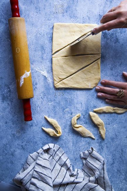 Hand cutting croissant dough