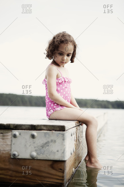 Young girl sitting on pier in her bathing suit