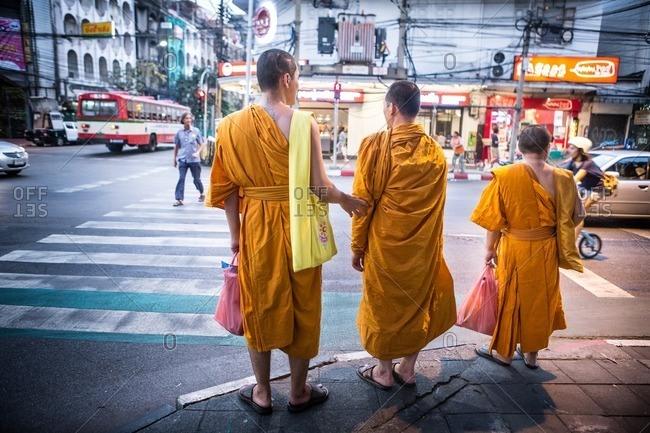 Bangkok, Thailand - January 25, 2015: Three monks on city corner