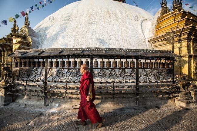Kathmandu, Nepal - April 19, 2015: Buddhist monk passing a stupa