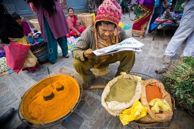 Kathmandu, Nepal - April 21, 2015: Spice vendor reading a newspaper