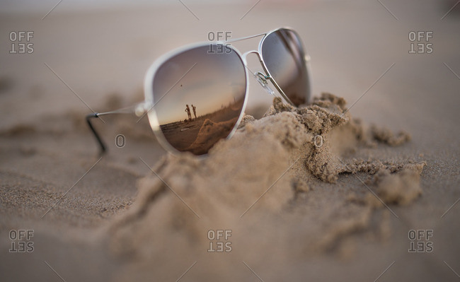 Close up of mirrored sunglasses on the sand with a reflection of people standing on the beach