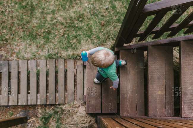 Boy walking down a wooden flight of stairs