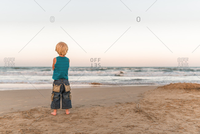Boy standing on a sandy beach looking out at the water