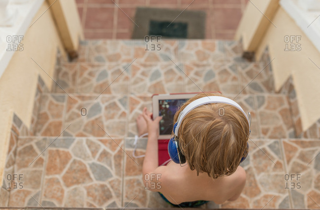 Little boy sitting on stairs using tablet and wearing headphones