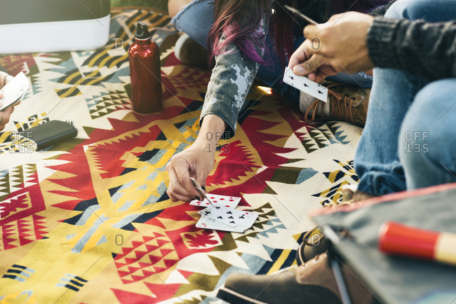 People playing a card game together while sitting on a blanket