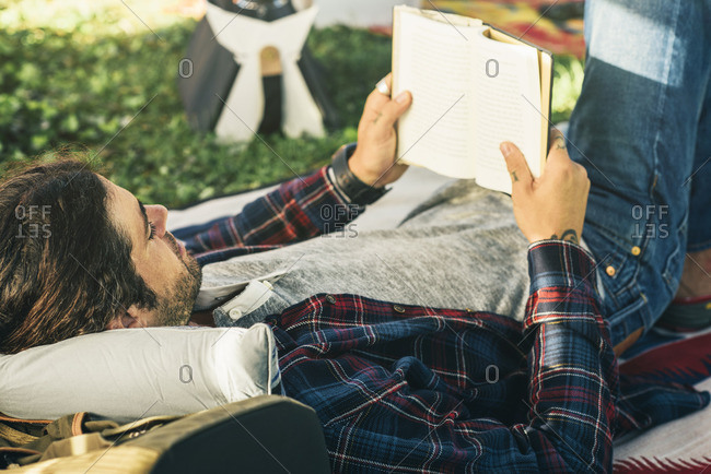 Young man reading a book while lying down outside