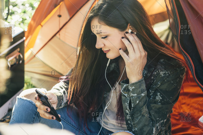 Young woman listening to music on her smartphone while sitting outside tent in a campground