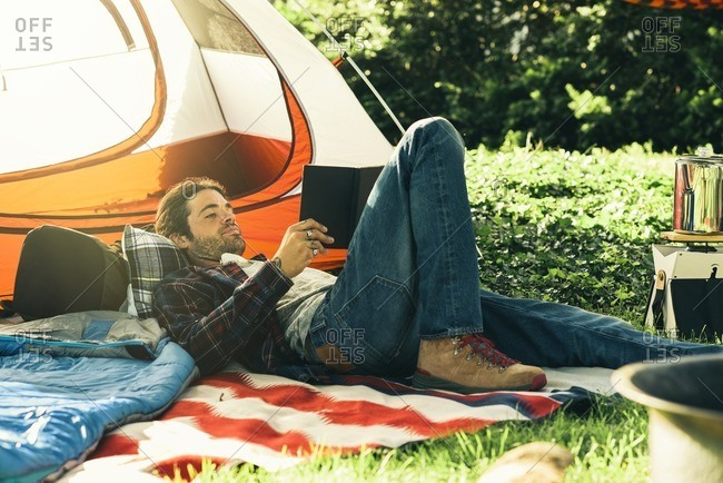 Young man reading a book while lying down outside tent in a campground
