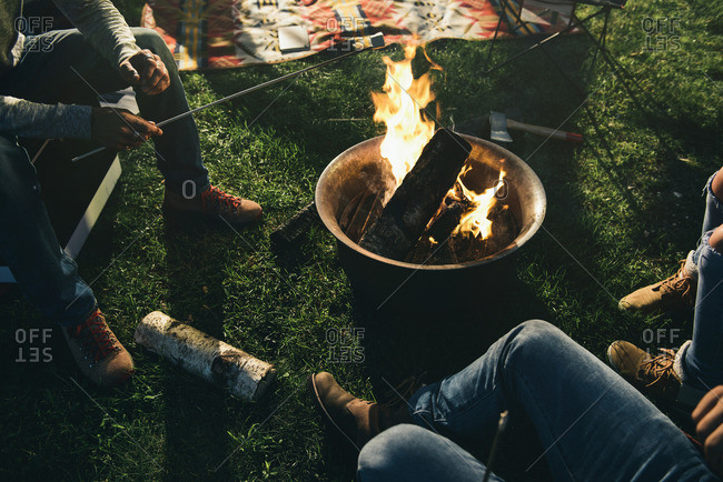 Camper roasting marshmallow over a campfire