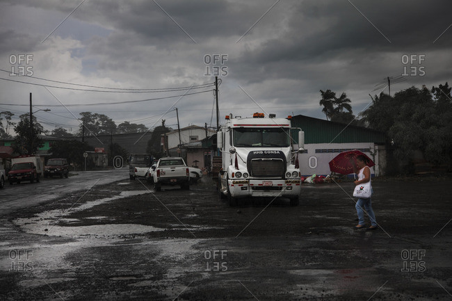 Canas, Costa Rica, Central America - August 31, 2014: A woman walking under the rain in a small town
