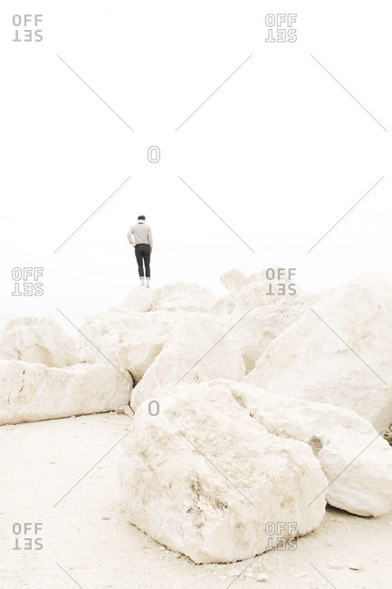 A man watching the sea from white rocks
