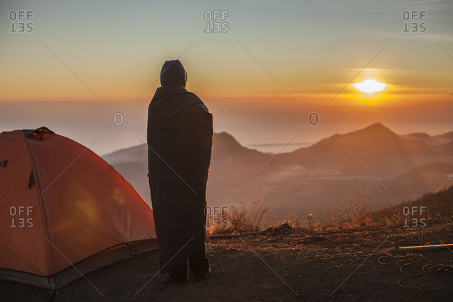 A girl watching the lake at sunrise next to her tent