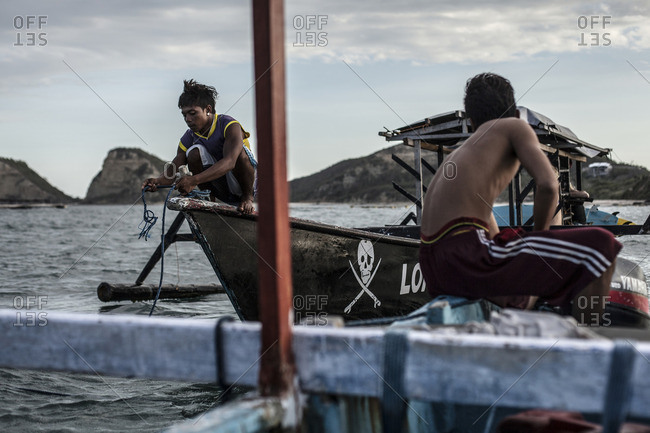 Gerupuk, Lombok, Indonesia - August 15, 2016: Two young men on local boats helping each other to arrive at the shore