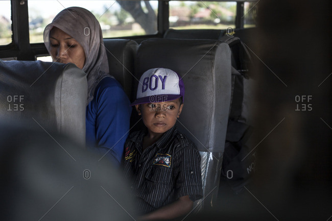 Sumbawa, Indonesia - August 22, 2016: A kid with his mother traveling by a local bus
