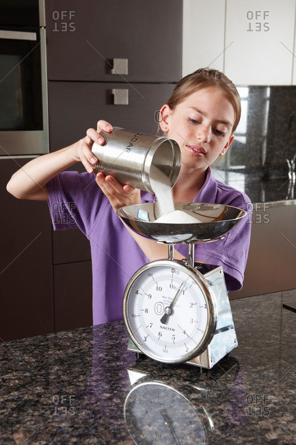 Girl weighing sugar on kitchen scales