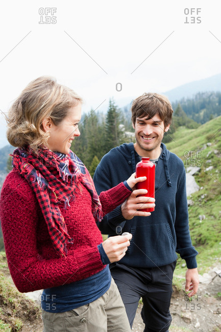 Man offering woman bottle