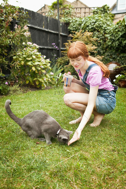 Woman feeding cat in garden