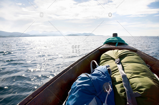 Bow of wooden boat with rucksacks