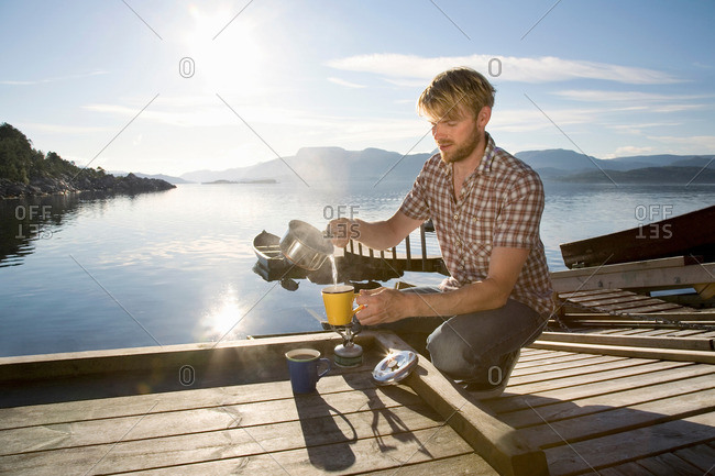 Man making coffee on jetty by sea
