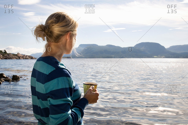 Woman with coffee by sea and mountains