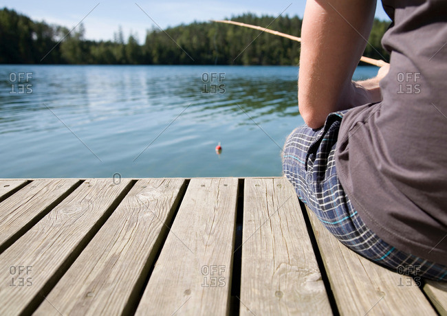 Man on jetty, fishing with bamboo rod