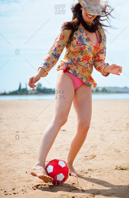 Woman playing soccer at the beach