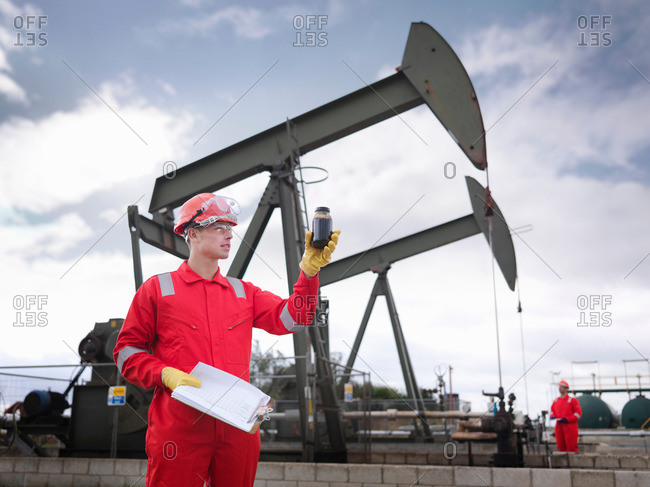 Worker inspecting crude oil sample next to oil pumps above onshore oil wells (nodding donkeys/pumpjacks), with second worker in background