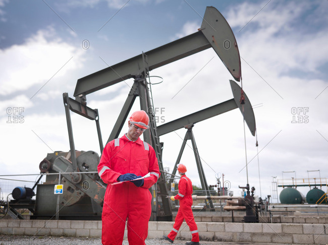 Workers next to oil pumps above onshore oil wells (nodding donkeys/pumpjacks). One worker in foreground holding clipboard, one in background looking up at pump