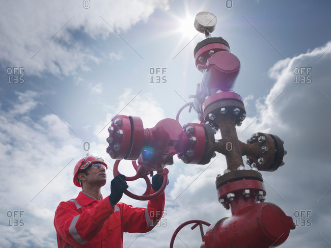 Worker turning valve on oil well 'christmas tree', looking up