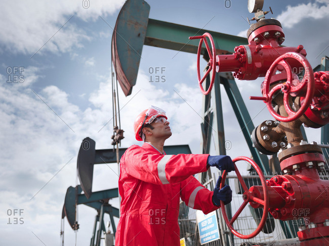 Worker turning valve on oil well 'christmas tree', looking up, with oil well pumps (nodding donkeys/pumpjacks) in background