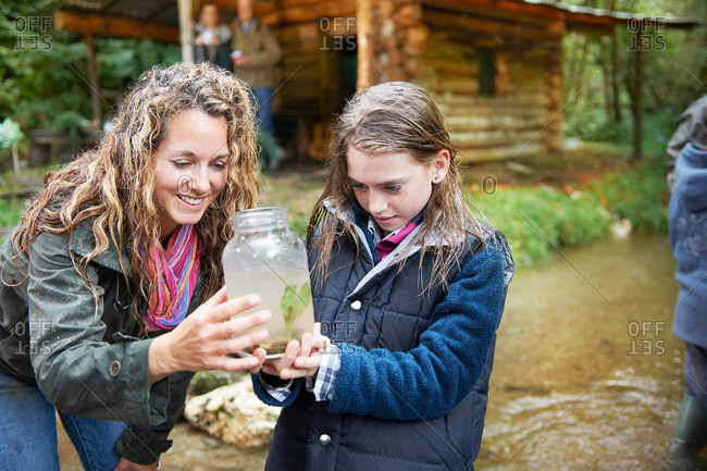 Mom and daughter examining insect in jar