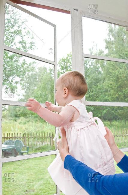 Mum holding baby at the window