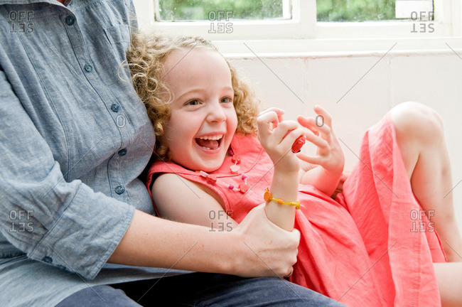 Girl laughing in Mum's arms