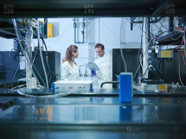Scientists talking and looking at notes in laboratory with laser experiment