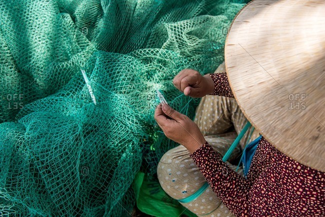 Vietnamese woman fixing fishing net