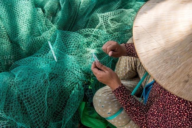 Vietnamese woman fixing fishing net
