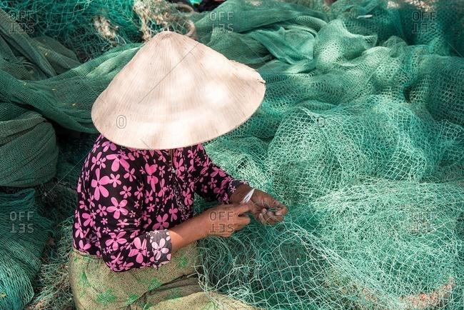 Vietnamese woman stitching fishing net