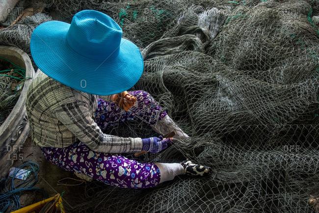 Vietnamese woman repairing fishing net