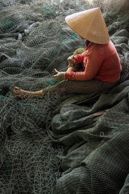 Vietnamese woman working on fishing net