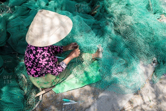 Woman stitching fishing net