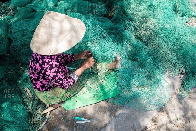 Woman stitching fishing net